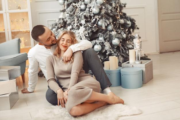 Couple élégant assis à la maison près de l'arbre de noël