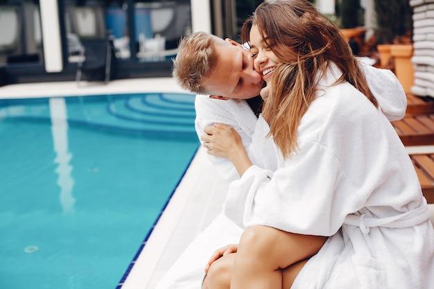 Couple élégant assis près d'une piscine