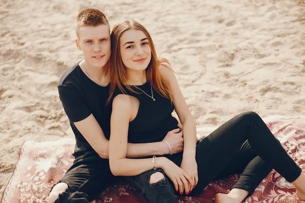 Un couple élégant et beau en vêtements noirs passe un bon moment sur la plage