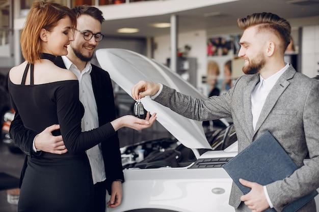 Couple élégant et élégant dans un salon de l'automobile