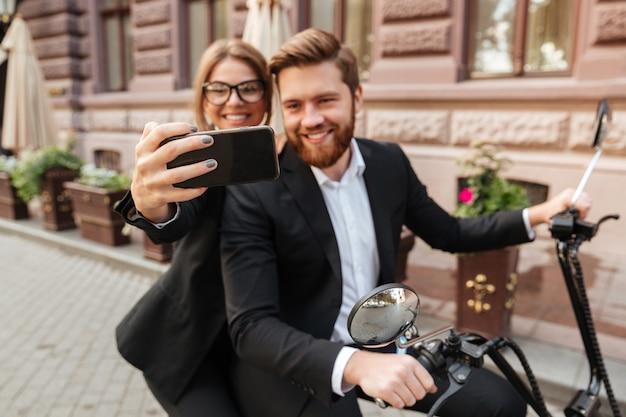 Couple élégant gai assis sur une moto moderne à l'extérieur
