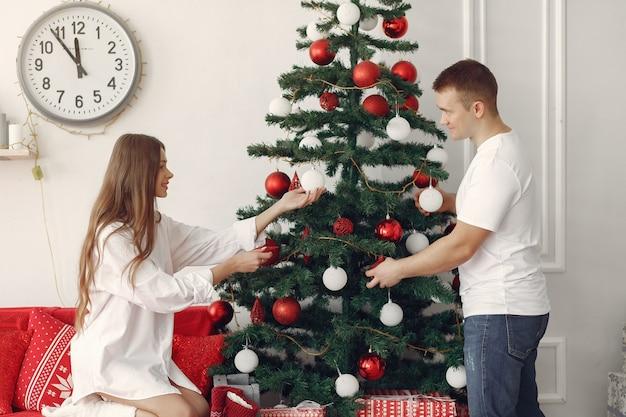 Couple élégant à la maison près de l'arbre de noël