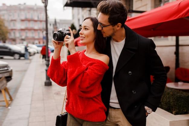Couple élégant à la mode amoureux marchant dans la rue pendant la date ou les vacances. femme brune en pull rouge, faire des photos par caméra.