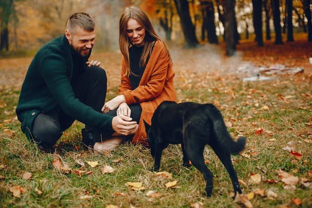 Couple élégant passe du temps dans un parc en automne