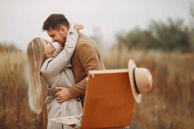 Couple élégant peinture dans un champ d'automne