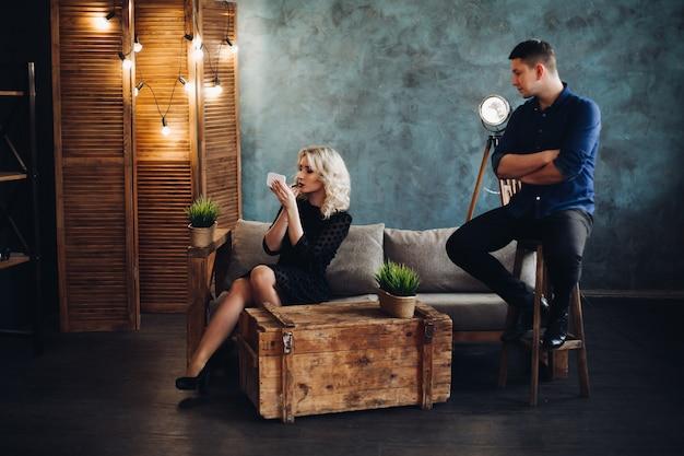 Couple élégant posant un studio décoré gris.