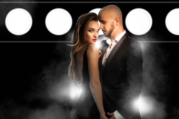 Couple élégant sexuel amoureux posant en studio sur un mur de fumée sombre