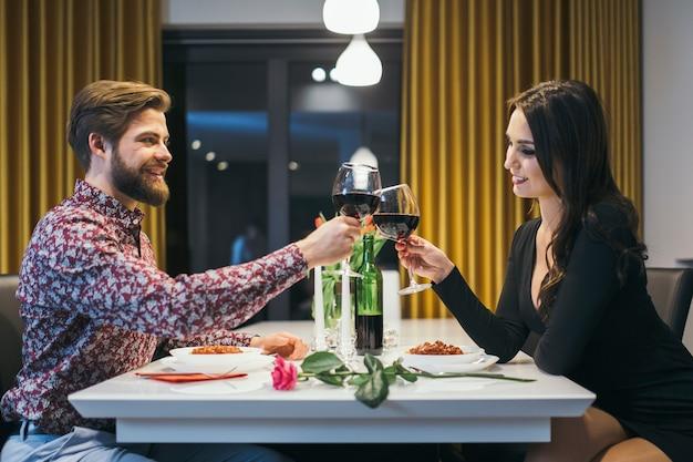 Couple élégant tinter avec des verres en train de dîner