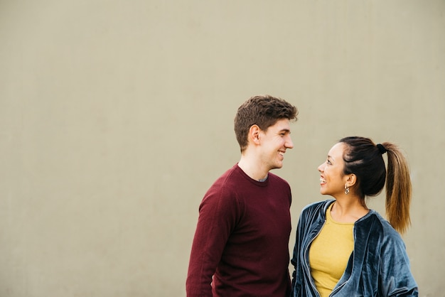 Couple embrassant multiethnique souriant et se regardant