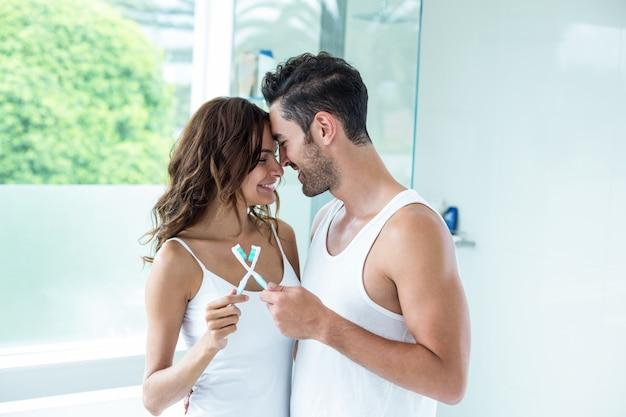 Couple embrassant tout en tenant la brosse à dents