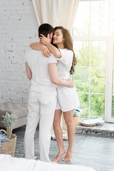 Couple embrassé à la maison à côté de la fenêtre