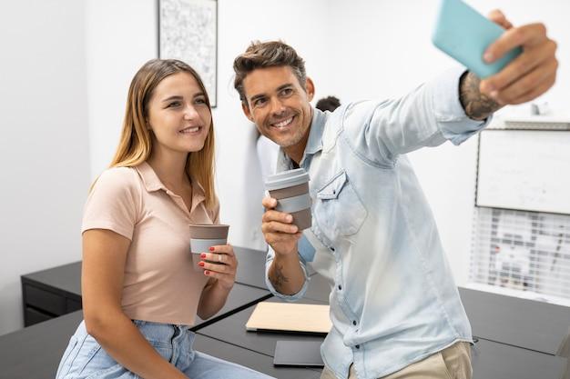 Un couple d'employés de bureau prend un selfie en buvant un café