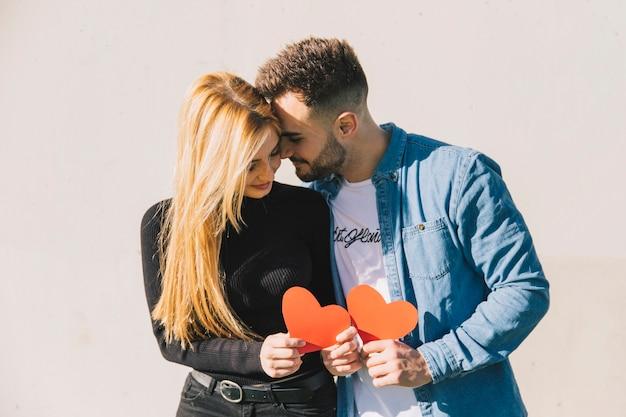 Couple énamouré tenant des coeurs de papier