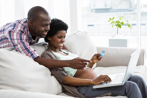 Couple enceinte, achats en ligne sur ordinateur portable à la maison