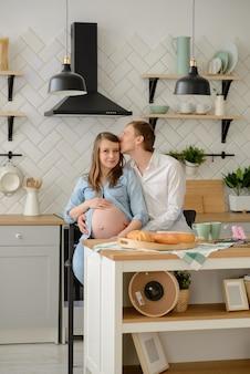 Couple enceinte amoureux assis dans la cuisine