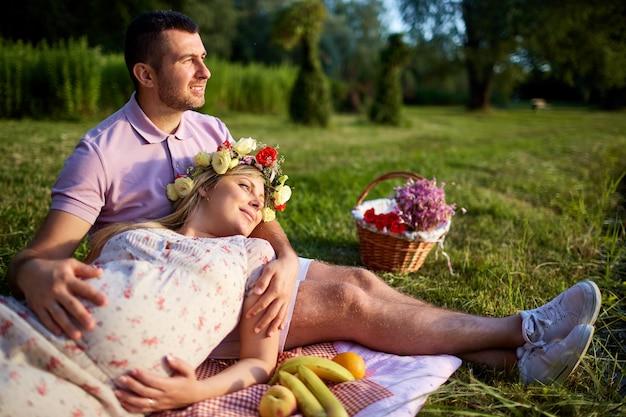 Couple enceinte sur parc naturel lors d'un pique-nique en été