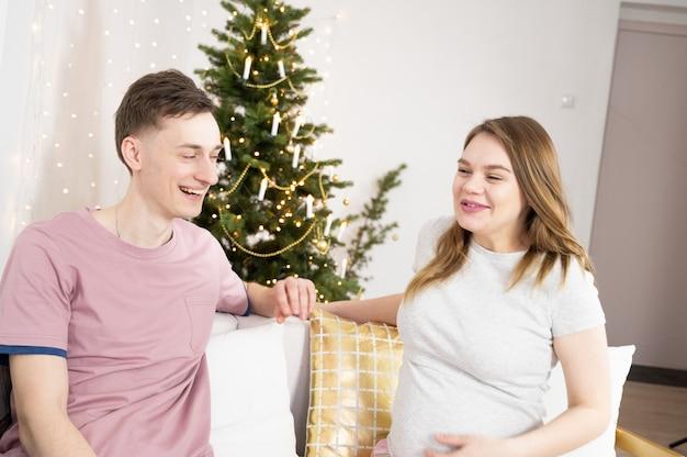 Couple enceinte souriant dans le salon. concept de grossesse, de vacances d'hiver et de personnes.