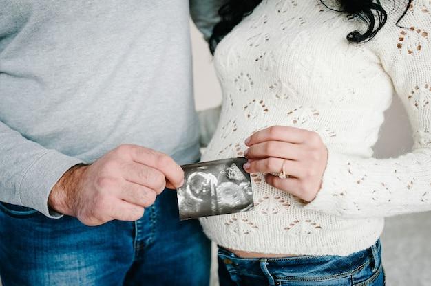 Couple enceinte tenant dans les mains échographie de leur bébé