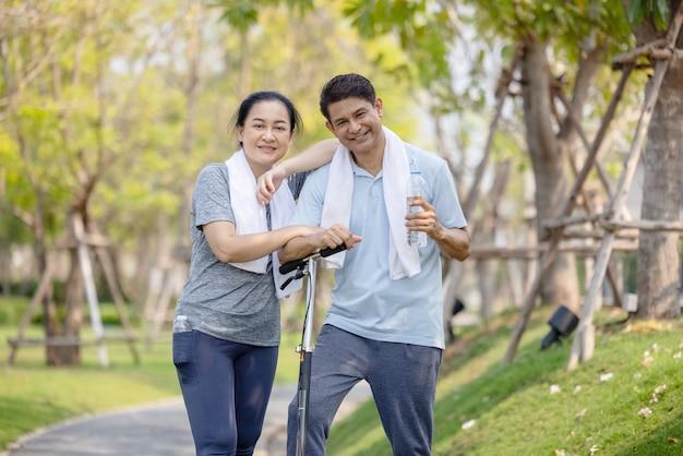 Couple d'entraînement et d'exercice avec scooter ensemble en plein air dans le parc