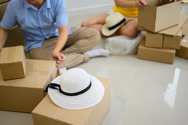 Un couple d'entrepreneurs thaïlandais emballe la boîte. vente en ligne et livraison à domicile. confinement et travail à domicile. nouvelle normalité et vie après covid.
