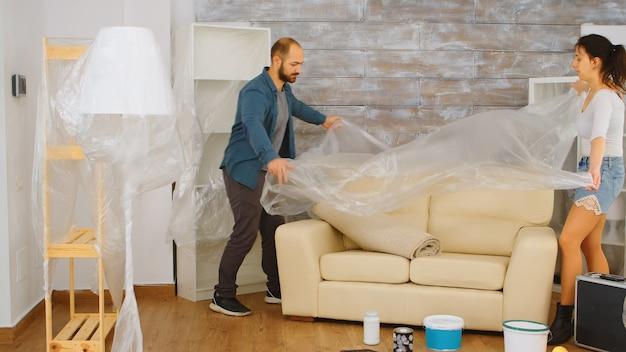 Couple enveloppant le canapé dans une feuille de plastique pour la protection pendant qu'ils rénovent le salon. travaux de rénovation, construction, peinture.