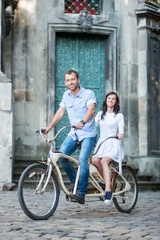 Couple, équitation, sur, vélo tandem, contre, bâtiment historique