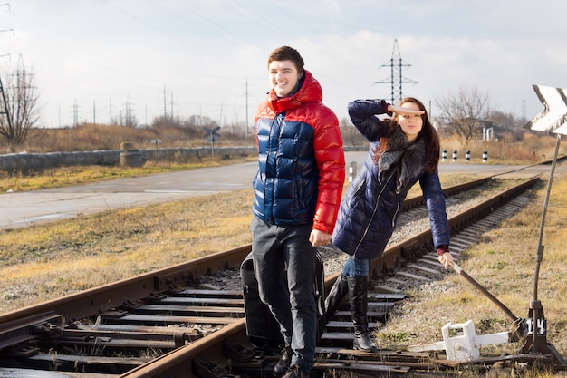 Couple espiègle attendant un train avec des bagages debout le long de la voie près d'un passage à niveau rural avec la fille saluant alors qu'elle tripote un levier