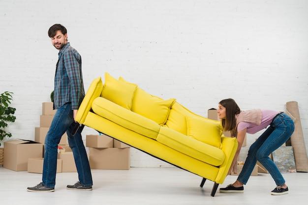 Couple essayant de placer le canapé jaune dans leur nouvelle maison