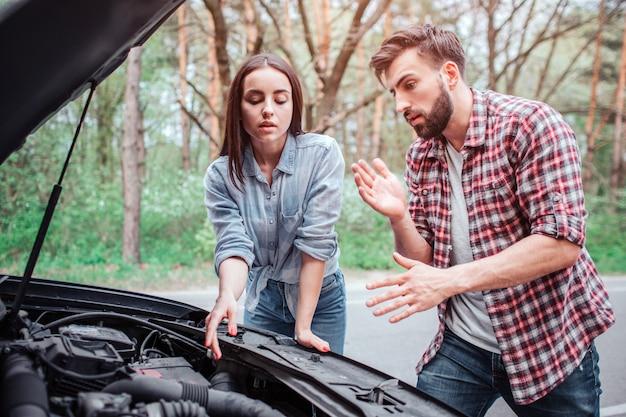 Couple essayant de réparer le moteur de la voiture