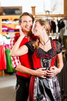 Couple essaye dirndl ou lederhosen dans un magasin