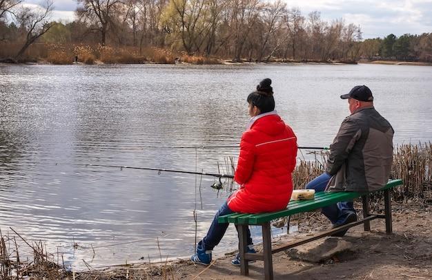 Le couple est assis sur un banc au bord de la rivière et pêche.