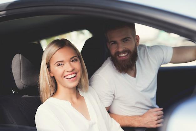 Couple est assis dans la cabine d'une voiture électrique confortable