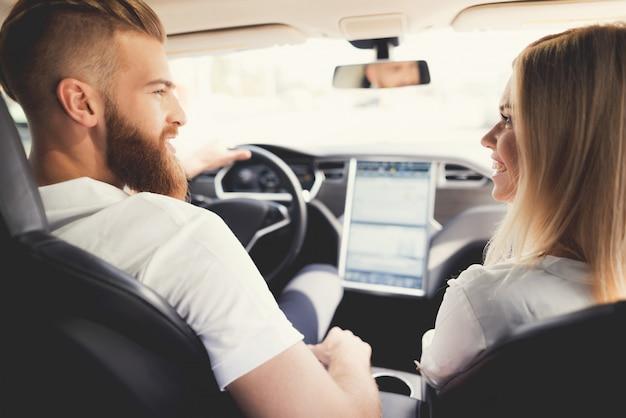 Couple est assis dans une voiture électrique moderne et confortable.