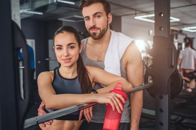 Couple est debout ensemble dans la salle de formation et pose devant la caméra