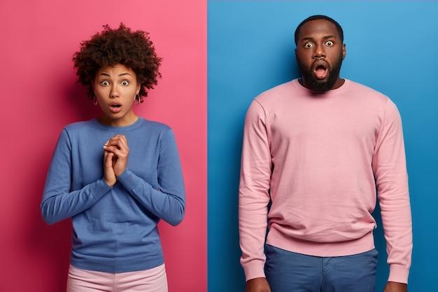 Un couple ethnique perplexe préoccupé regarde avec un grand choc, étant anxieux et effrayé de voir un accident terrifié