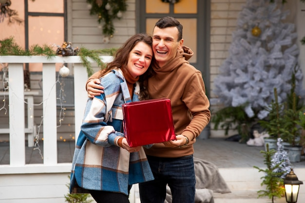 Couple étreignant et célébrant le nouvel an à l'extérieur. ils tiennent une boîte rouge avec le cadeau de la saint-valentin