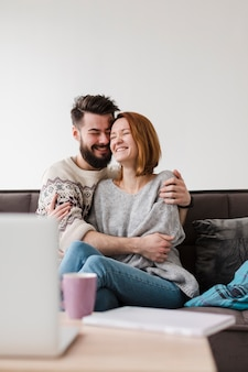 Couple étreignant et décor flou avec ordinateur portable