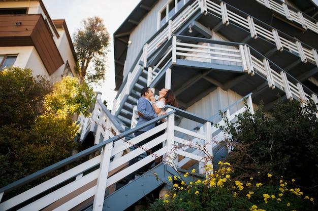 Couple étreignant sur l'escalier de la grande maison, un mec brune indienne étreint une fille asiatique.