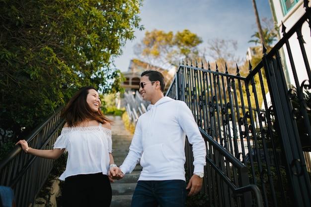 Couple étreignant sur l'escalier, un mec brune indienne étreint une fille asiatique.
