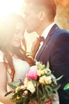 Couple, étreindre, à, coucher soleil, couple amoureux, s'embrasser