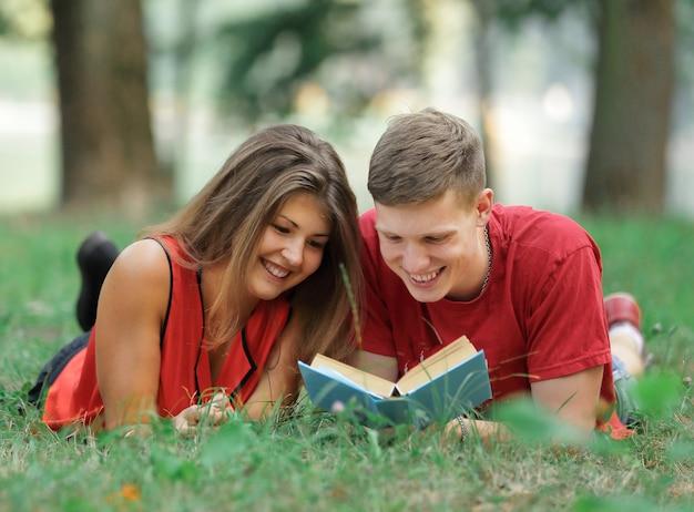Couple d'étudiants allongés sur l'herbe dans le parc et lisant un livre.