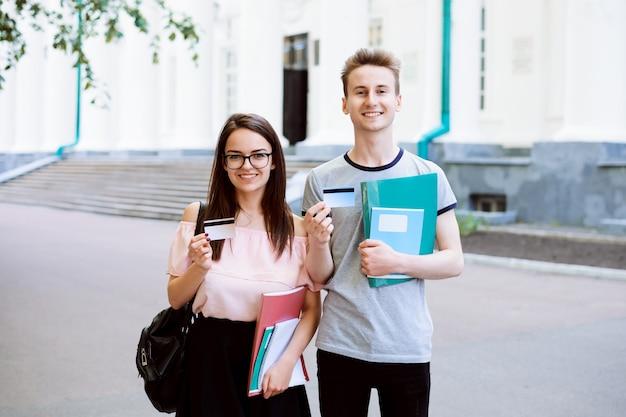 Couple d'étudiants debout à l'extérieur, souriant, regardant vers l'avant et montrant la carte de crédit