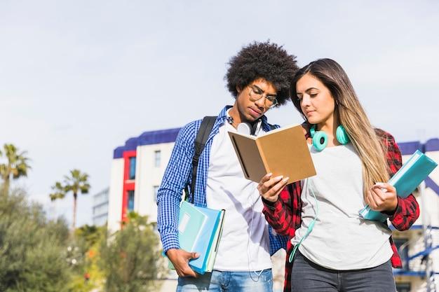 Couple d'étudiants divers debout devant le bâtiment de l'université en lisant le livre