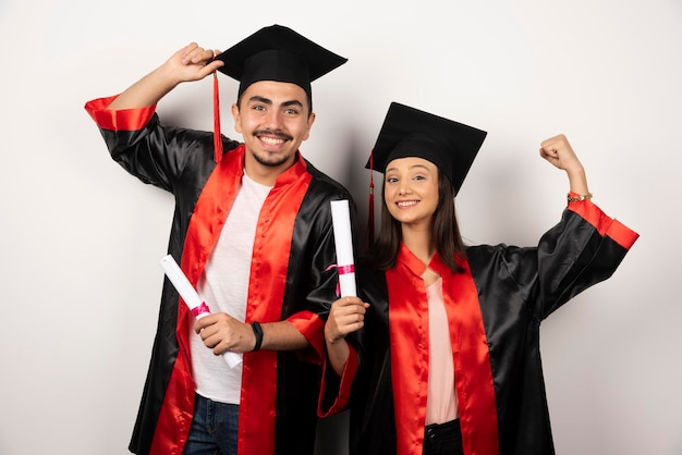 Couple d'étudiants en robe se sentant heureux avec leur diplôme sur blanc.