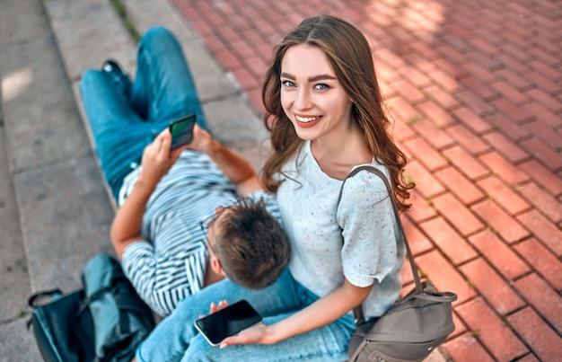 Un couple d'étudiants avec des sacs à dos et un ordinateur portable est assis sur les marches à l'extérieur du campus et utilise leur smartphone.