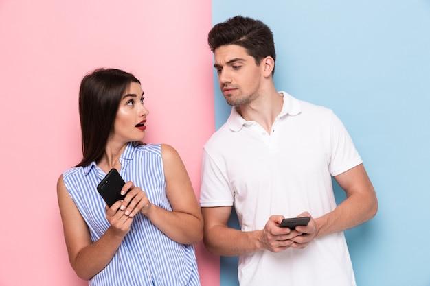 Couple européen à l'aide de smartphones ensemble, isolé sur mur coloré