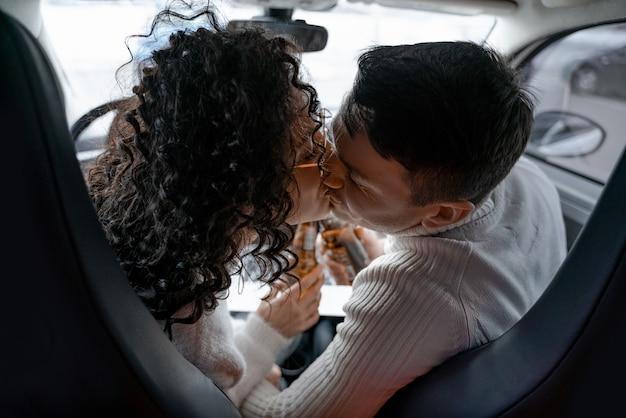 Couple européen s'embrassant dans une automobile personnelle. jeune belle femme bouclée dans des verres et homme adulte amoureux. concept de profiter du temps ensemble