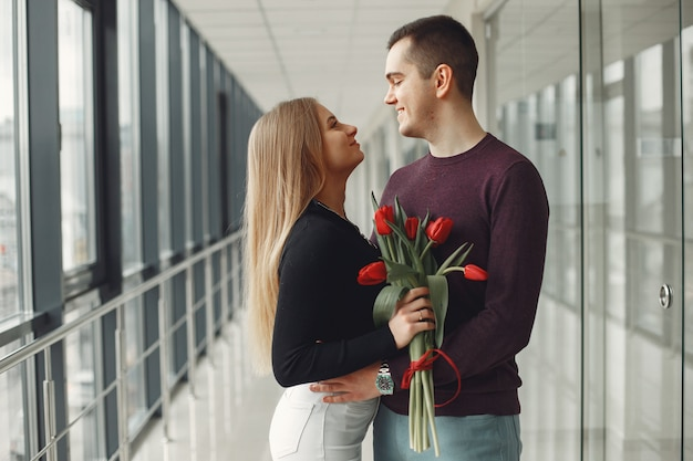 Couple européen se tient dans une salle avec un tas de tulipes rouges