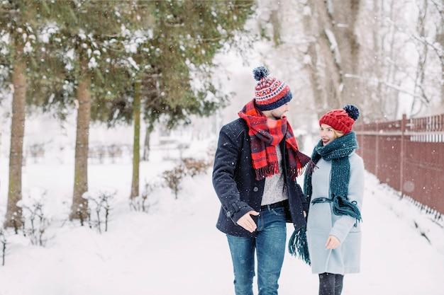Couple excité en amour courir dans les chutes de neige