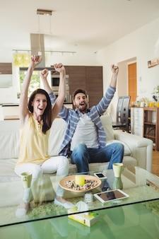 Couple excité devant la télé ensemble